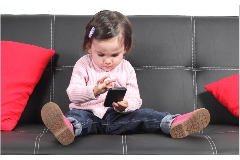 Little girl focusing on her mobile. Body awareness is lost through focusing and too little movement.